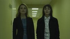 Two businesswomen standing in corridor in office building Stock Footage