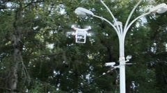 Camera shoot flying quadrocopter in summer park Stock Footage