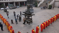 Monks wearing orange robes take part in a ceremony in Shanghai, China - stock footage