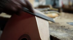 Craftsman sanding wood with wood file from a construction guitar, slider shot Stock Footage