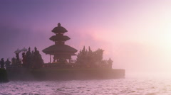 Scenic background of beautiful Bali temple in mist on lake under sunset sunlight Stock Footage