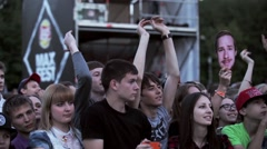 Audience watch on stage, raise hands, apploud. Boy look in camea. Live fest Stock Footage