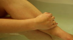 Female washes legs in the bath Stock Footage