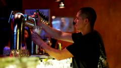 Bartender pours a glass of foamy beer in a nightclub. - stock footage