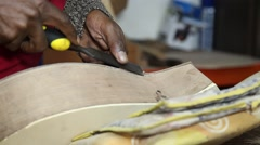 Craftsman  using chisel in guitar that is being made - stock footage
