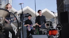 Rock music band perform on stage at live festival. Guitarists, drummer Stock Footage