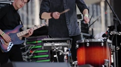 Rock band perform on stage at live festival. Soloist knocks drumsticks on drums Stock Footage