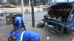 City workers throw waste bags into the back of garbage truck in Shanghai, China Stock Footage
