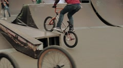 Boy make extreme trick on BMX bicycle in skate park. Audience apploud Stock Footage