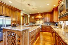 Brilliant kitchen with stained wood cabinets and hardwood floor. - stock photo