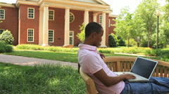 happy male african university student outdoors - stock footage