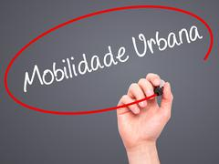 Man Hand writing Mobilidade Urbana (Urban Mobility in Portuguese with black m Stock Photos
