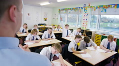 4K Young students listening to teacher & putting hands up in school classroom Stock Footage