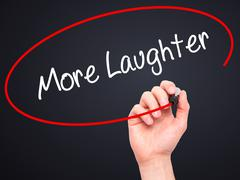 Man Hand writing More Laughter with black marker on visual screen - stock photo