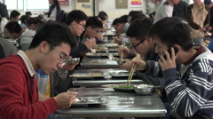 Students use smartphones,  lunch in school canteen, Shanghai University in China Stock Footage