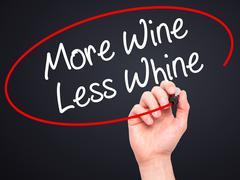 Man Hand writing More Wine Less Whine with black marker on visual screen - stock photo