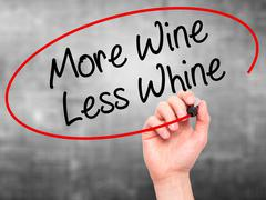 Man Hand writing More Wine Less Whine with black marker on visual screen Stock Photos