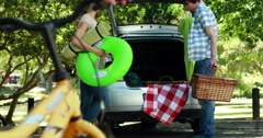 Family placing things in the trunk of the car Stock Footage