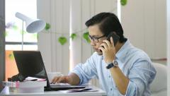 Asian Man Calling and Typing at Office - 4K Resolution Stock Footage