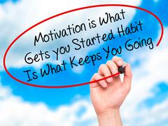 Man Hand writing Motivation is What Gets you Started Habit Is What Keeps You  Stock Photos