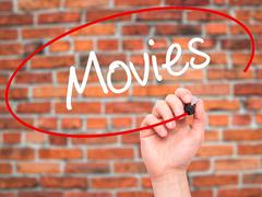 Man Hand writing  Movies with black marker on visual screen - stock photo