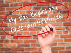 Man Hand writing My Day Begins and Ends with Gratitude with black marker on v Stock Photos