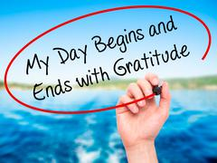 Man Hand writing My Day Begins and Ends with Gratitude with black marker on v - stock photo