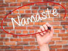 Man Hand writing Namaste with black marker on visual screen - stock photo