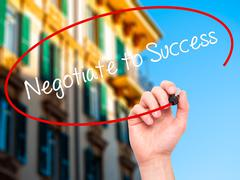 Man Hand writing Negotiate to Success with black marker on visual screen - stock photo