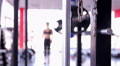 Defocused silhouette of fit woman training in gym, doing squats with barbell HD Footage