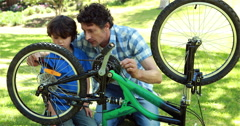 Father and son fixing bike Stock Footage