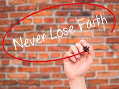 Man Hand writing Never Lose Faith with black marker on visual screen - stock photo