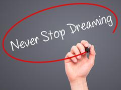 Man Hand writing Never Stop Dreaming with black marker on visual screen - stock photo