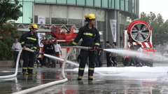 Two Chinese firefighters wearing protective gear spray water during a fire drill Stock Footage