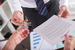 Realtor giving house keys to his client - stock photo