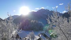 Aerial - Above snowy trees into the sun behind mountains Stock Footage