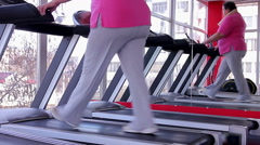 Tired overweight woman sweating on treadmill after intensive workout in the gym - stock footage