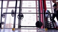 Female athlete bending forward with heavy barbell, woman exercising in the gym Footage