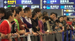 People wait for friends, family, at arrivals hall Shanghai airport China Stock Footage