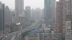 Traffic drives through residential apartment buildings in central Shanghai China Stock Footage