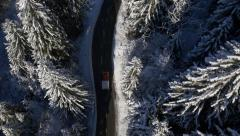 Aerial, vertical - Car driving on sunlit road in winter Stock Footage