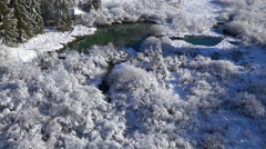Aerial - Water spring of deep, brilliant green color in snow Stock Footage