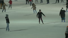 Young people ice skating on Christmas in the City Park of Budapest at night Stock Footage