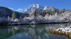 Aerial - Over water towards snow capped mountains Stock Footage
