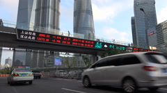 Traffic drives under electronic ticker board in business district Shanghai Stock Footage