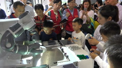 Chinese kids play a game against a robot, technology trade fair in Shanghai Stock Footage