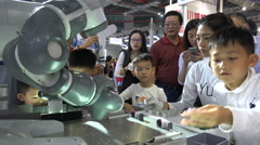 Curious children play game against robot at technology show Shanghai, China Stock Footage