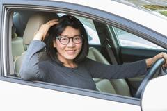 Asian woman driving car lookiing to camera with smiling face happiness emotio Kuvituskuvat