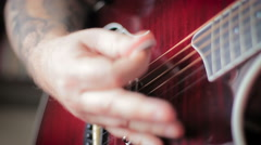 Man with Tatoo playing acoustic guitar Stock Footage