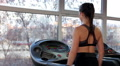 Beautiful lady with sexy fit body walking on treadmill, warming up for workout HD Footage